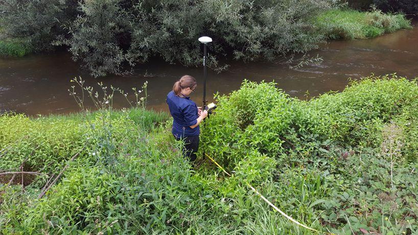 Lyndsey standing in green bush near a flowing river