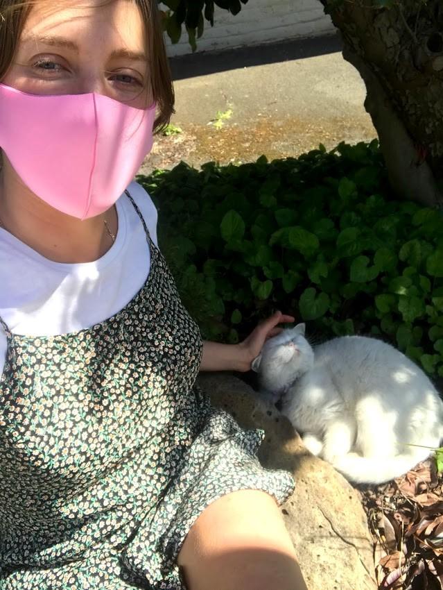 Graduate Ella Loefller wearing pink mask and patting white cat